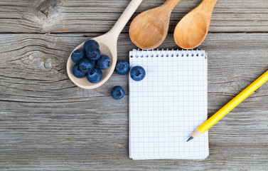 top view of recipe book with fresh Blueberries ingredients on wo