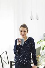 Jungen Frau mit Kaffeebecher arbeitet zu Hause