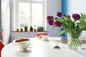 Frühstückstisch mit Tulpen, Croissants und Kaffee