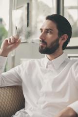 Junger Mann raucht Zigarillo