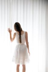 Junge Frau berührt einen weißen Vorhang, Blick zurück