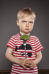Böse schauender kleiner Jungen, die Gabel mit Brokkoli vor sich