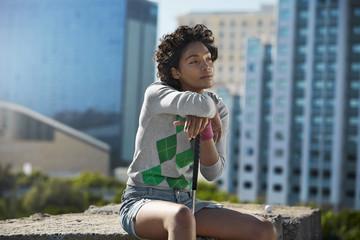 Junge Frau stützt sich auf Golfschläger in der Stadt