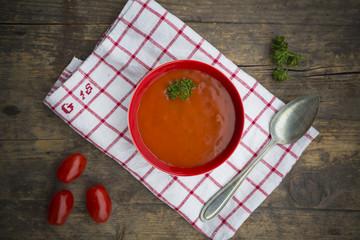 Schüssel Tomatensuppe auf Küchentuch und Holztisch