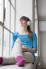 Junge Frau sitzt auf der Fensterbank in einem Büro und hört Musik mit Kopfhörer
