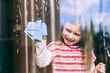 Lächelndes Mädchen putzt Fenster