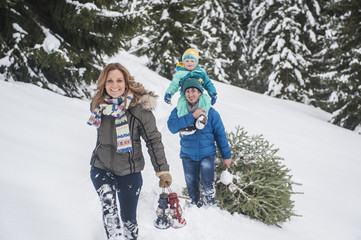 Österreich, Land Salzburg, Altenmarkt-Zauchensee, Familie läuft im Schnee, mit Weihnachtsbaum