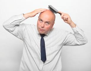 Hairless man combing his head.