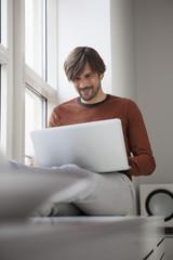 Mann mit Laptop auf der Fensterbank sitzend
