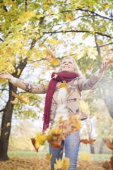 Polen, Warschau, Blonde Frau wirft Blätter im Herbst