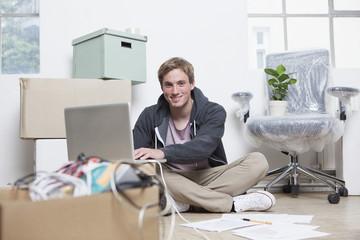 Junger Mann sitzt auf dem Boden zwischen Kartons in einem Büro