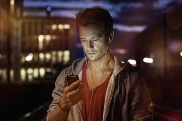 Junger Mann mit Smartphone und Kopfhörern, Musik hören in der Nacht