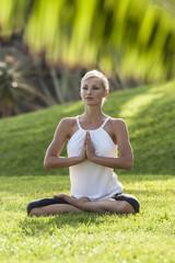 Frau praktiziert Yoga auf Wiese