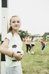 Teenager-Mädchen mit Fußball lehnt an Torpfosten