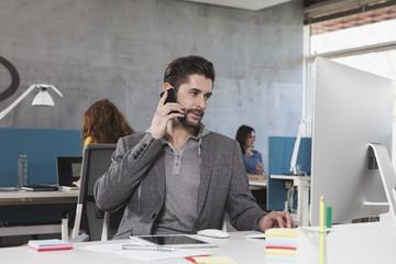 Mit Smartphone am Arbeitsplatz im Büro