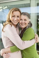 Mutter und ihre Tochter umarmen sich vor ihrem Haus