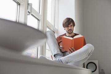 Mann liest Buch, sitzend auf Fensterbank