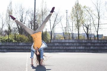 Junge Frau macht einen Handstand