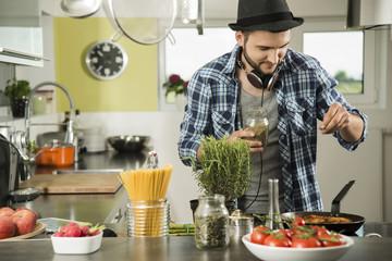 Junger Mann in der Küche, kocht zu Hause