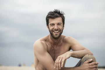 Lachende cooler Mann mit nacktem Oberkörper