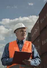 Mann mit Klemmbrett und reflektierender Weste im Containerhafen