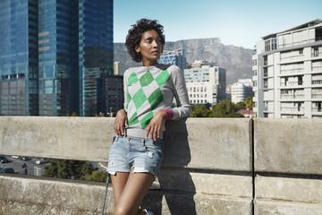 Junge Frau lehnt an Betongeländer in der Stadt
