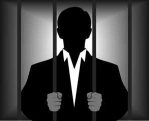 silhouette of a man behind bars