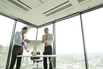 Zwei Geschäftsleute im neuen Büro, Einstellen des Computer-Monitors