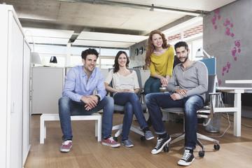Gruppenbild der vier kreativen Menschen im Büro sitzend