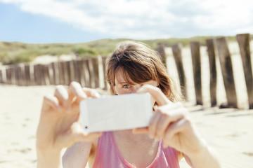 Frau fotografiert mit ihrem Smartphone am Strand