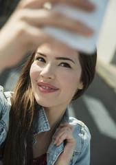Brünette junge Frau, die ein Selfie im Freien macht