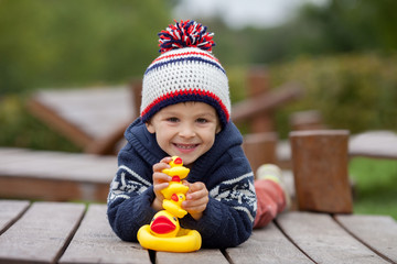 Adorable little boy, playing with rubber ducks outside on an aut