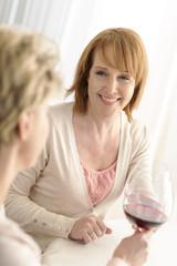 Lächelnde reife Frau stößt mit ihrer Freundin an