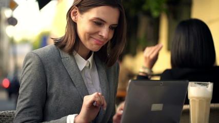 Businesswoman with laptop having coffee break, sitting in cafe