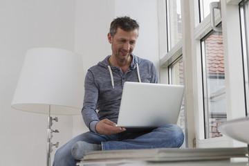 Mann sitzt auf der Fensterbank mit Laptop