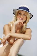 Lächelnde junge Frau mit Sommerhut