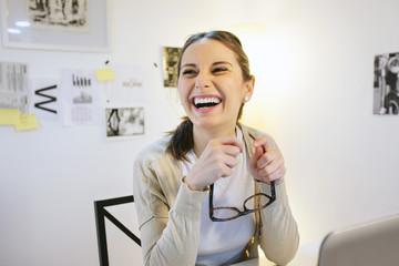 Lachende Frau im modernen Büro zu Hause