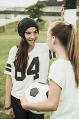 Zwei Mädchen im Teenageralter, sprechen auf Fußballplatz