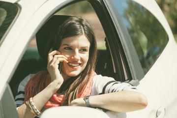 Spanien, Barcelona, Junge Frau im Auto mit Handy