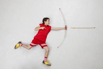 Junge schiesst mit Pfeil und Bogen