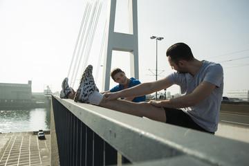 Junger Mann und Teenager bei Stretching auf der Brücke