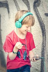 Portrait des glücklichen Jungen mit Smartphone und Kopfhörern