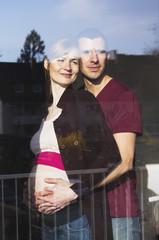 Paar erwartet ein Baby, schaut aus dem Fenster
