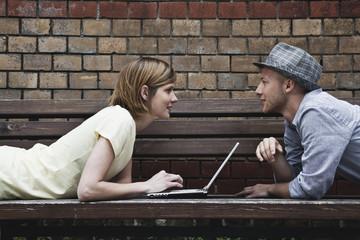 Mann und Frau liegen auf der Bank und mit Laptop