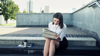 Young attractive businesswoman reading newspaper on stairs in th