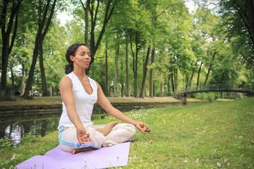Frau trainiert Yoga in einem Park, Meditation