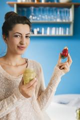 Junge schwangere Frau isst Erdbeeren mit Senf in ihrer Küche