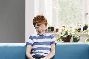 Junge sitzt auf blauer Couch im Wohnzimmer