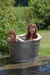 Mädchen badet in einer Zinkwanne
