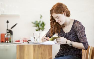 Junge Frau mit Notizbuch, Schreiben im Café